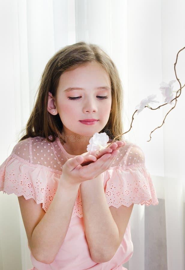 公主礼服的女孩嗅到花 免版税库存照片