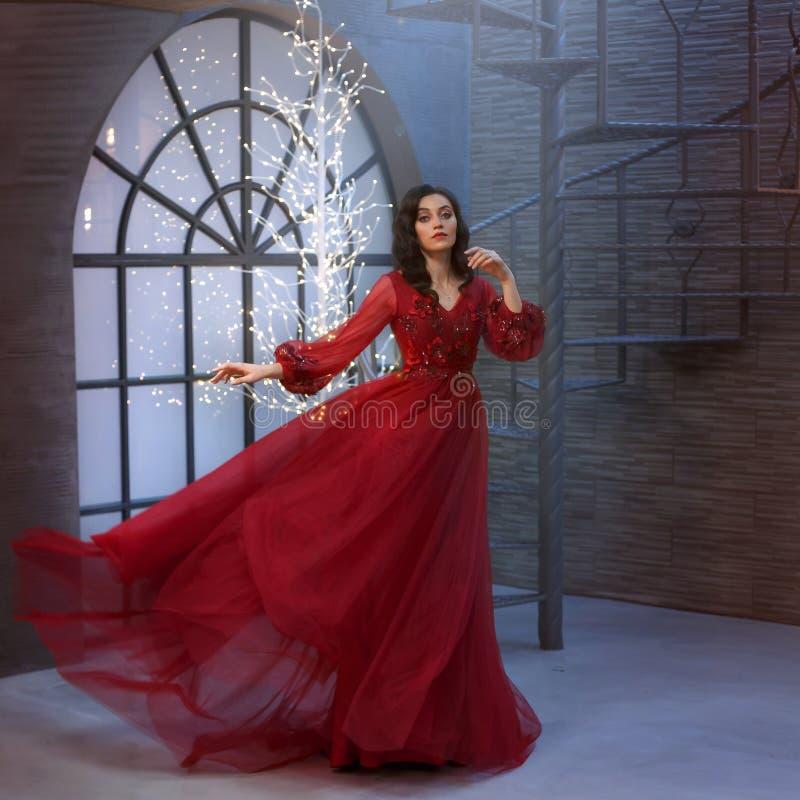公主舞蹈、豪华美妙的礼服在红色容易地飞行和振翼,女王/王后的典雅的运动的 免版税库存照片