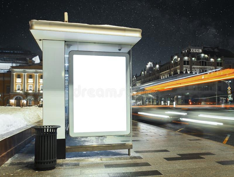 公交车站在与空白白色有启发性海报的城市晚上 库存照片