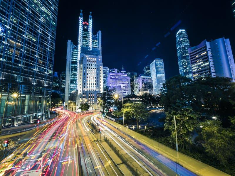 公共汽车、汽车和电车在一条香港市街道上的光足迹有的保留左标志 免版税库存图片