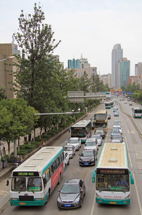 公共汽车和汽车在昆明,中国继续前进路 免版税库存图片
