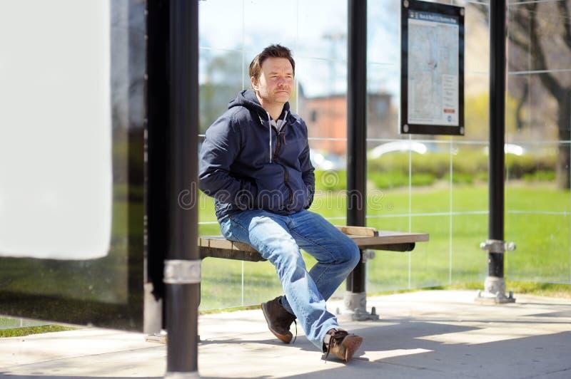 公共汽车站的中年人 库存照片