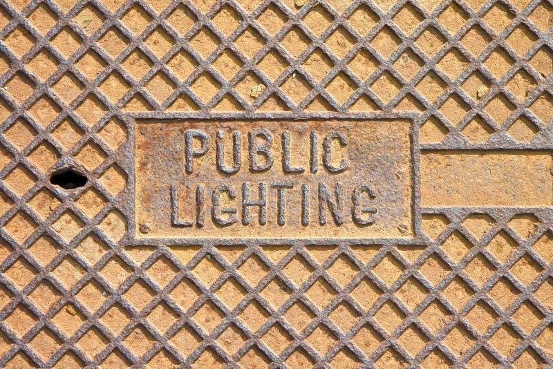 公共结构和公众的生锈的生铁人孔盖 免版税库存图片