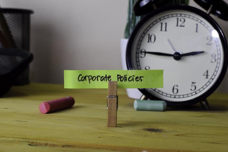 公司政策 在稠粘的笔记的手写在木办公桌上的服装扣子 库存图片