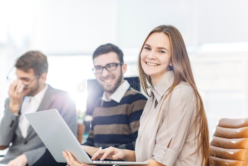 公司有坐在现代办公室的大厅的膝上型计算机的` s雇员 库存图片