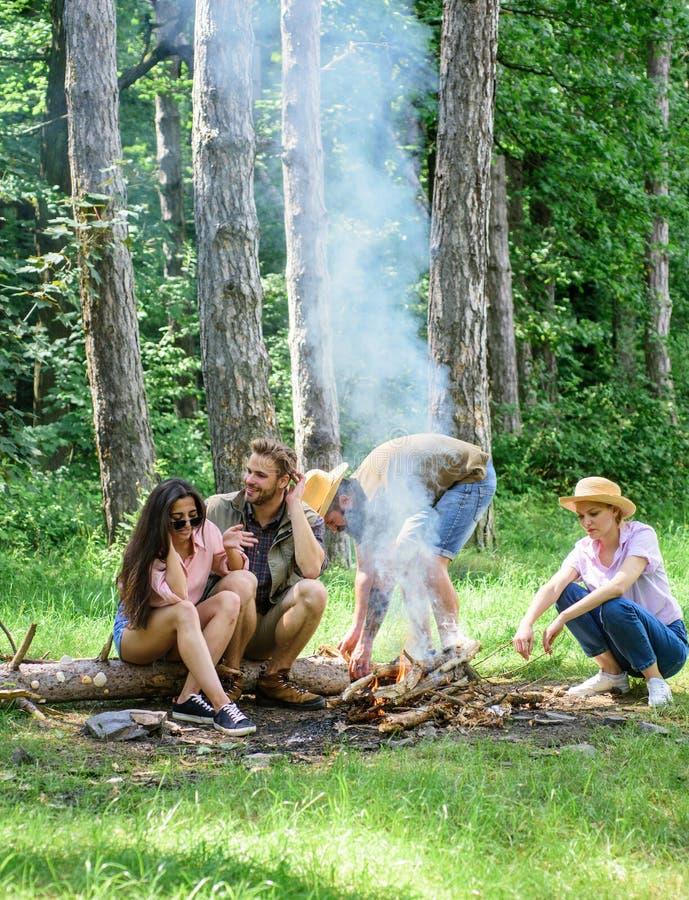公司朋友在篝火附近去野餐或烤烧烤食物 最好的朋友花费休闲周末高涨烤肉森林 免版税图库摄影