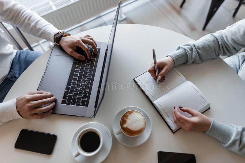 公司的专业成功的经理坐与膝上型计算机并且采访咖啡馆的女孩经理 免版税库存照片