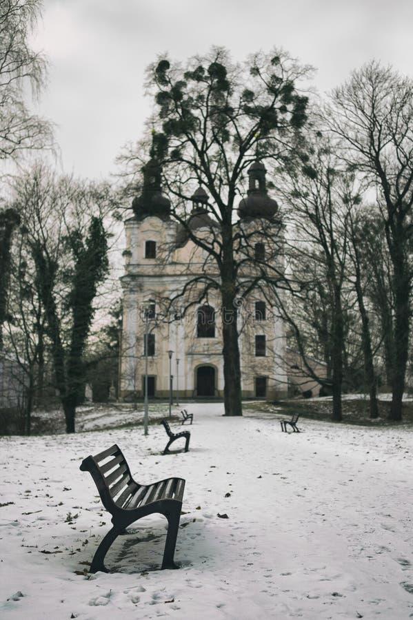 公园、长凳、路、光秃的树和教会 免版税图库摄影
