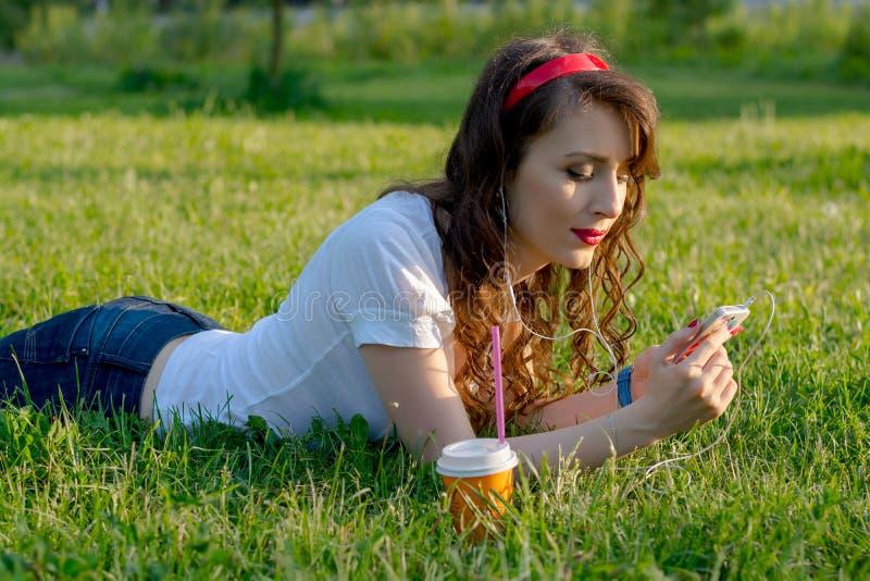 公园佩带的耳机的女孩有手机和杯子的  免版税库存照片