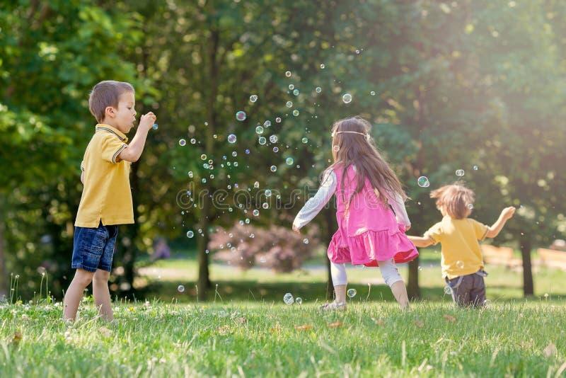 公园吹的肥皂泡和有乐趣的三个孩子 库存图片