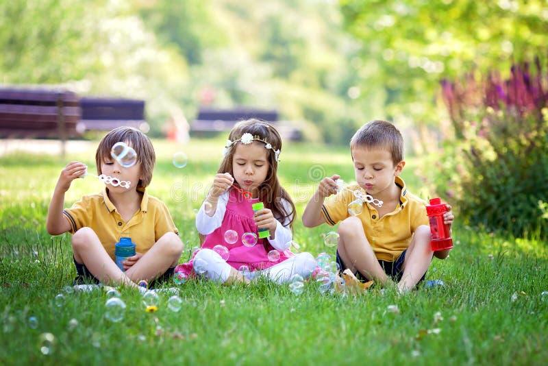 公园吹的肥皂泡和有乐趣的三个孩子 免版税图库摄影