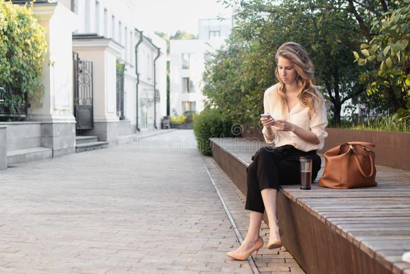 公园的年轻可爱的妇女,急忙与电话一起使用,饮用的咖啡,吃午餐 企业概念照片 图库摄影