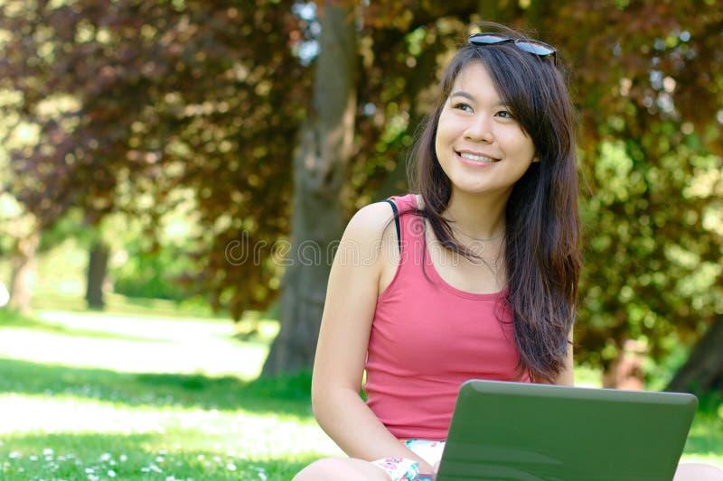 公园的微笑的亚裔女孩 免版税库存照片