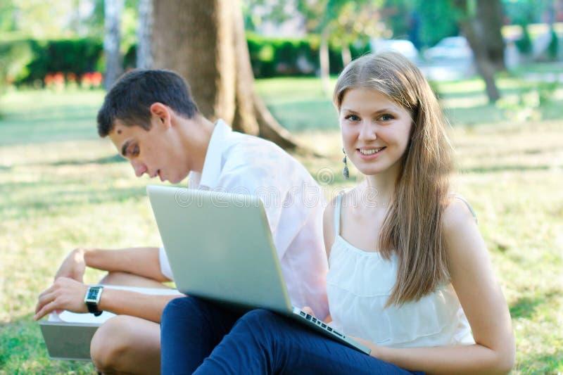公园的微笑的年轻女学生 库存照片