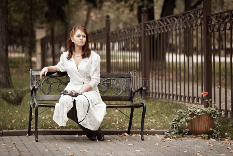 Download 公园的红头发人女孩 库存图片. 图片 包括有 女孩, 成人, 四十年代, 影子, 手袋, 放松, 礼服, 纵向 - 22352313