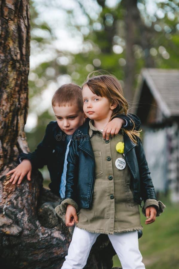 公园里两个漂亮的小孩,对着大树干的底部 免版税库存图片
