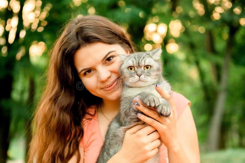 公园里漂亮的褐发美女正和一只猫坐在一起 在街上拍一只宠物猫的快乐照片 免版税图库摄影