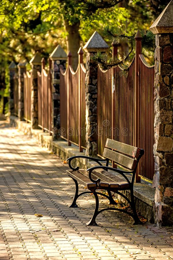 公园长椅在秋季太阳的一个城市 库存照片