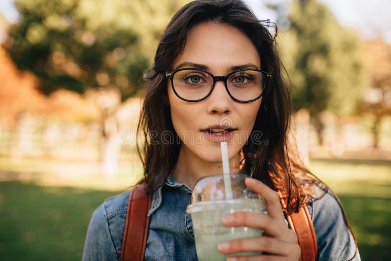 公园饮用的汁液的妇女 免版税图库摄影