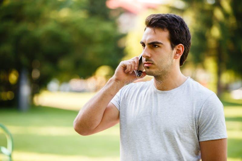 公园talkig的英俊的年轻人在他的电话 库存照片