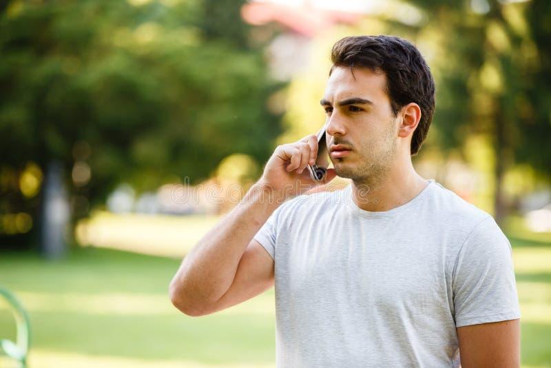 公园talkig的英俊的年轻人在他的电话 库存图片