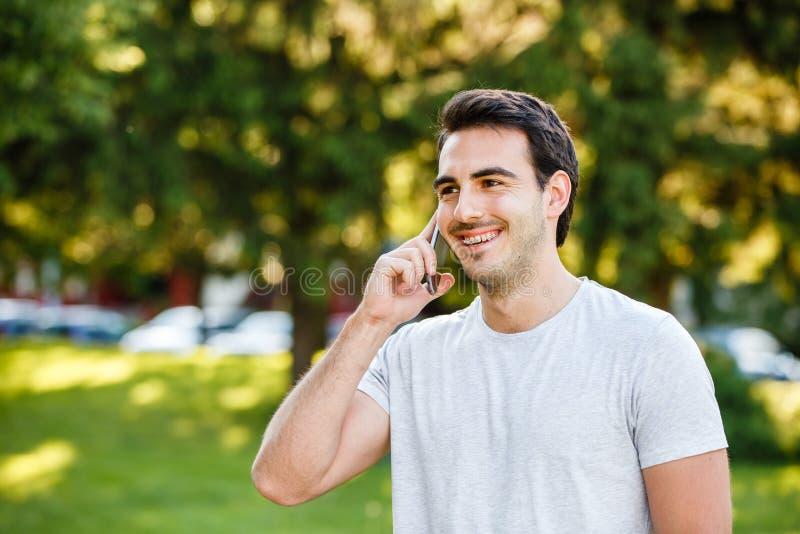 公园talkig的英俊的年轻人在他的电话 免版税库存图片