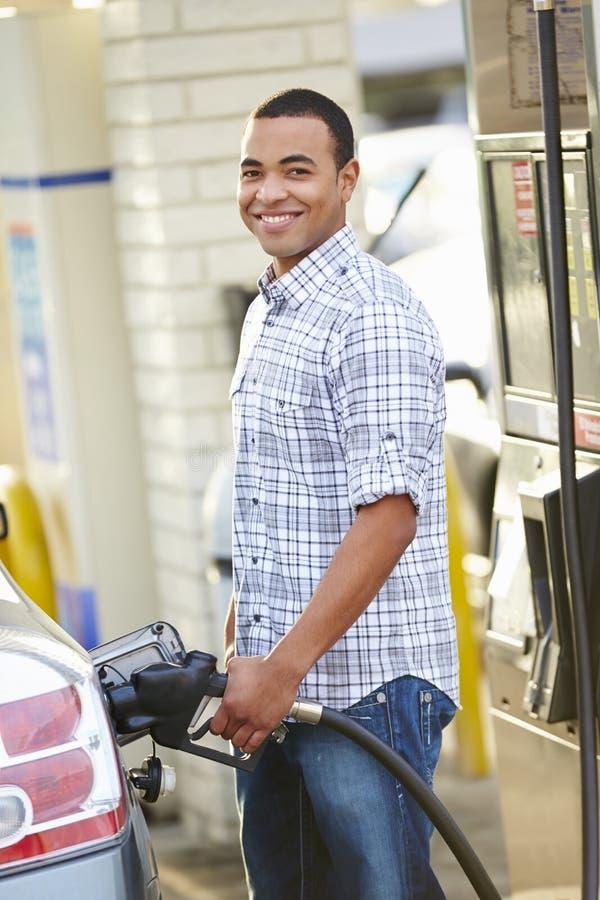 公在加油站的司机填装的汽车 免版税库存图片