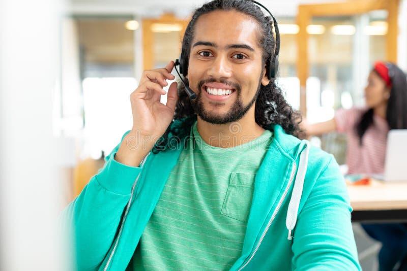 公客服执行委员看照相机和谈话在耳机在一个现代办公室 免版税库存图片