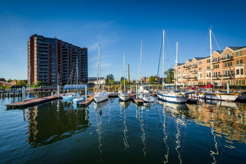 公寓和小船在小行政区的江边靠了码头 免版税库存照片