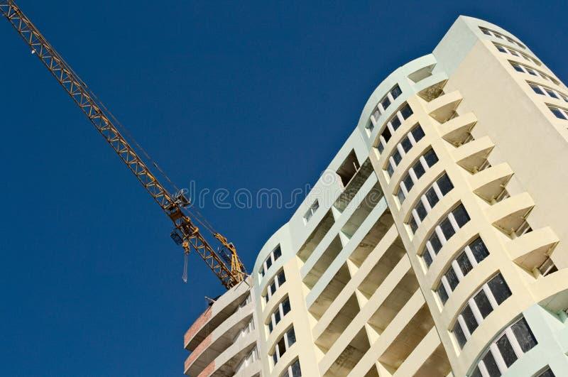 公寓工地工作与起重机机械的反对天空蔚蓝 免版税库存图片
