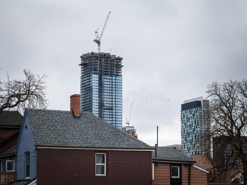 公寓房有它的起重机的摩天大楼工地工作,当小屋和居民住房是可看见的时,在街市多伦多 免版税库存照片