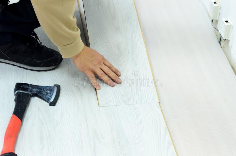 公寓的整修,放置层压制品的地板的人在屋子里 免版税库存照片