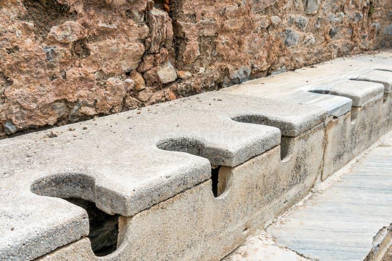 公开多位子洗手间大理石石头和岩石在壮观的古色古香的废墟在以弗所塞尔丘克的伊兹密尔,土耳其 历史古老 免版税库存图片