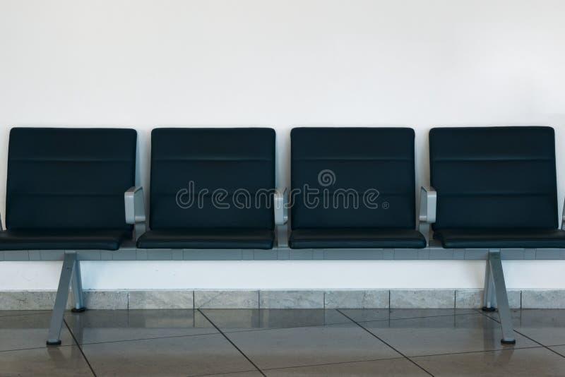公开安装的机场内部 在白色墙壁背景的蓝色空的就座 库存图片