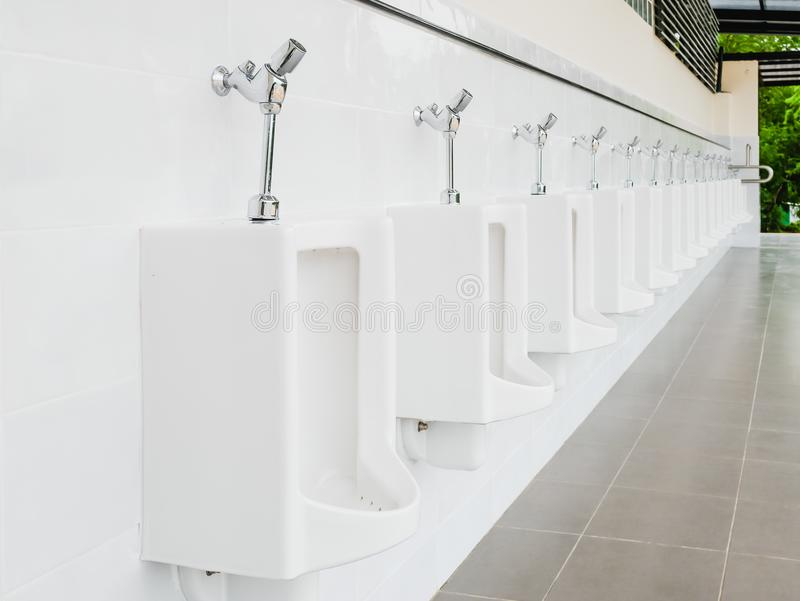 公开干净的现代白色男性洗手间,有尿壶的休息室 库存照片