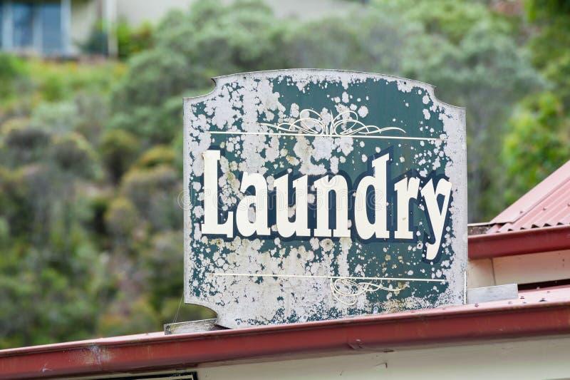 公开洗衣店的老退色的绿色洗衣店标志 免版税图库摄影