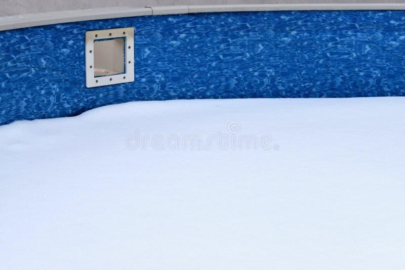 公开的游泳池在冬天,在水池里面是雪 免版税库存照片