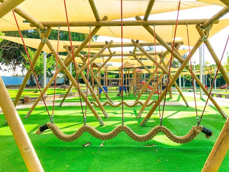 公开` s操场在城市 围场的五颜六色的操场在公园 停放与套现代孩子操场背景 库存照片