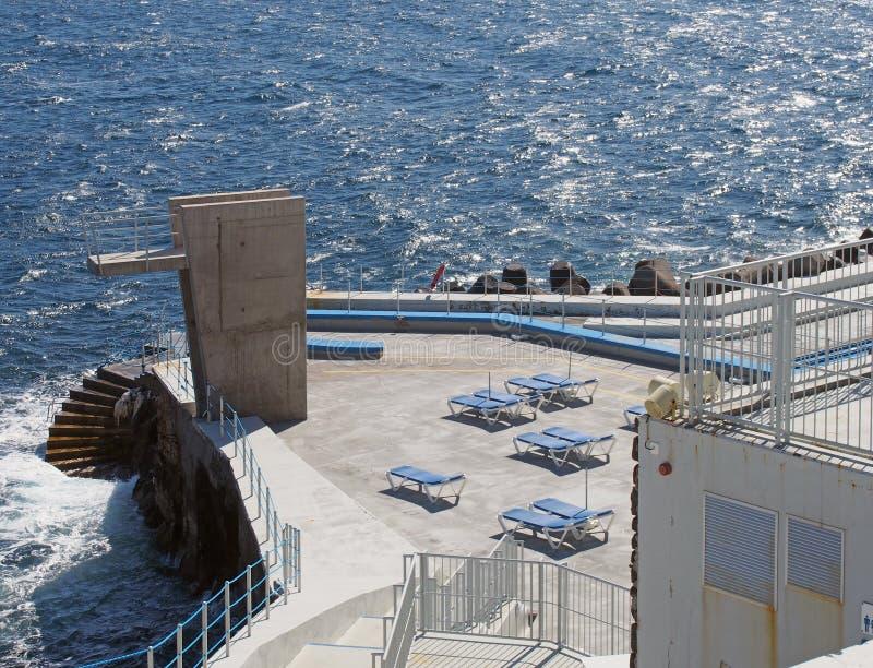 公开lido在有具体跳台太阳懒人的丰沙尔马德拉和步向被日光照射了蓝色海 库存图片