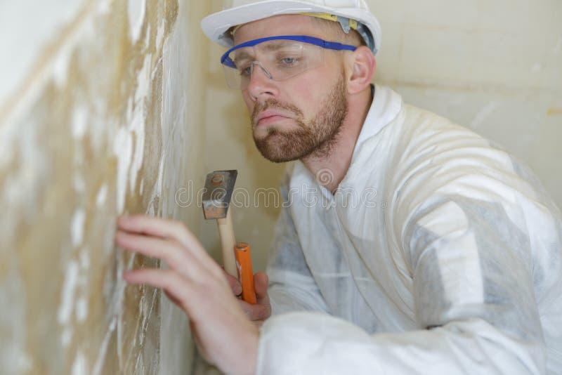 公承包商毁坏有锤子和凿子的砖墙壁 免版税库存图片