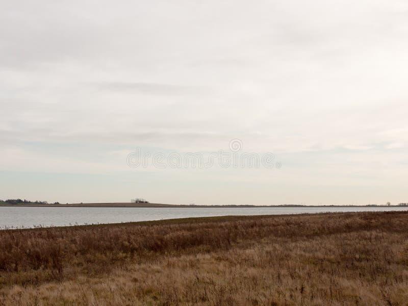 公海与草的海岸平原在清楚前面天际的阴云密布 免版税库存照片