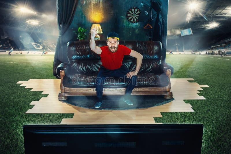 公爱好者坐沙发和观看的电视在橄榄球场中间 库存照片