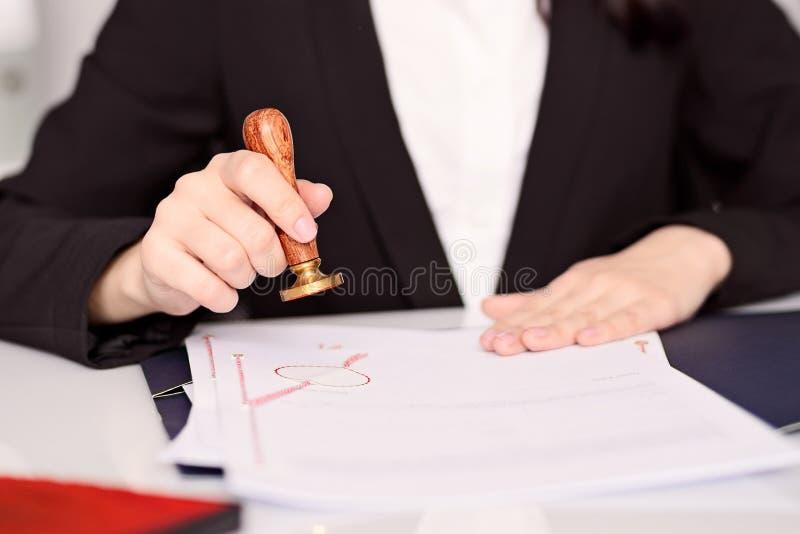 公证人盖印公证员行动的妇女手 库存图片
