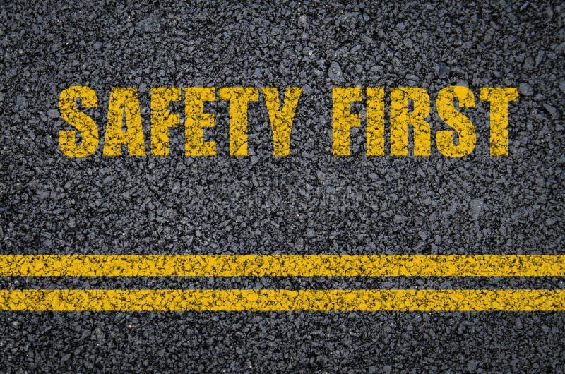 公路安全概念:在沥青的安全第一与中心线 免版税图库摄影