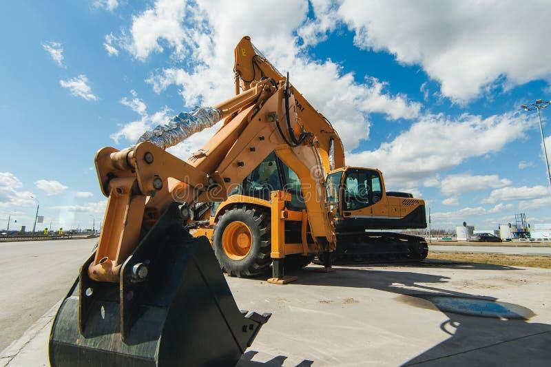 公路建筑物机械,拖拉机染黄在露天的挖掘机在运作的位置 库存照片