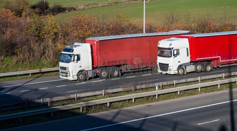 公路运输-在机动车路的两辆卡车 免版税库存图片