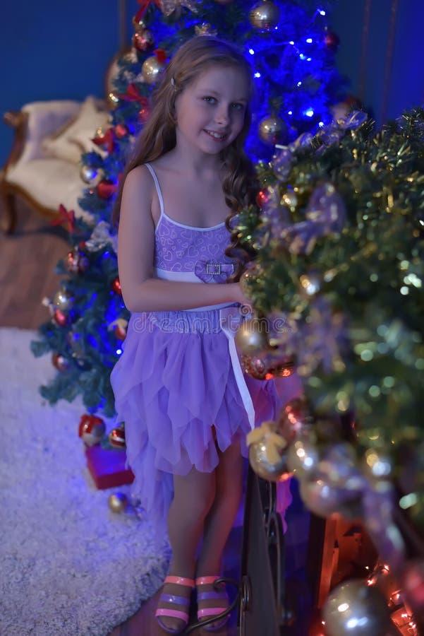 公主礼服的逗人喜爱的小女孩在圣诞树 免版税库存图片