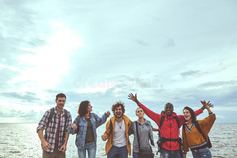 六个伙计是愉快的关于他们的旅途对海边 免版税库存照片