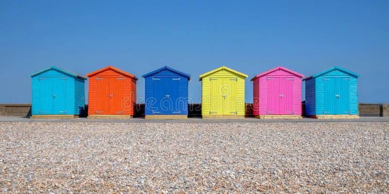 六个多彩多姿的海滩小屋线在Seaford海滩的,在前景是后面地面的Pebble海滩是清楚的蓝色 库存图片