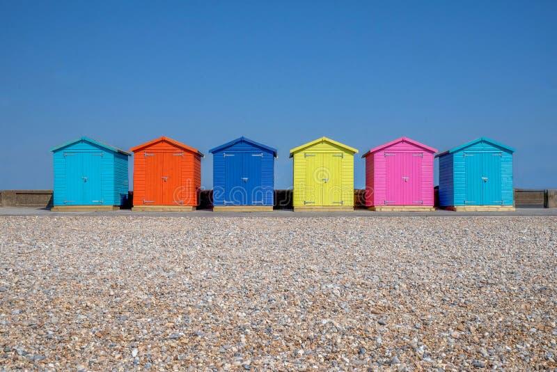 六个多彩多姿的海滩小屋线在Seaford海滩的,在前景是后面地面的Pebble海滩是清楚的蓝色 免版税库存照片